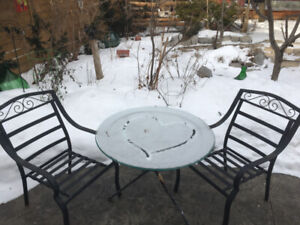 4 exterior metal chairs with cushions and glass table.