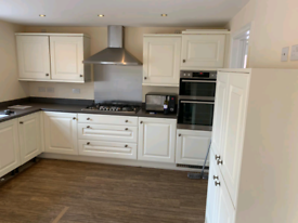 Fitted kitchen with worktops, sink, extractor fan, gas hob and splash