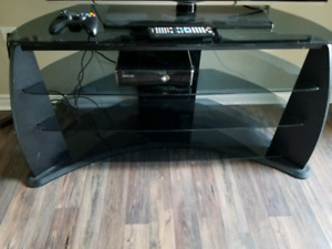 Large TV stand with glass shelves.