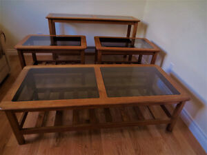 SET OF FOUR TEAK/ SMOKED GLASS OCCASIONAL TABLES