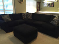 Black fabric sectional with sofa bed and ottoman