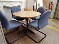 Round meeting room table with 4 blue chairs