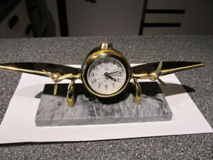 Brass airplane mantle clock, set on marble.