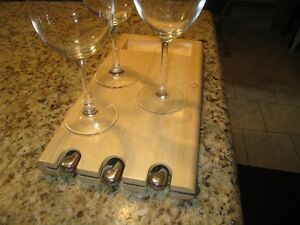 new wooden cheese board with various knifes and 3 wine glasses