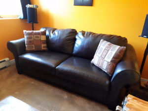 Brown faux leather sofa and two pillows