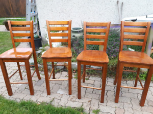 Four tall  solid wood kitchen or dining room chairs.