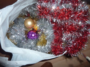 Grocery bag full of tinsel garlands plus a few ornaments