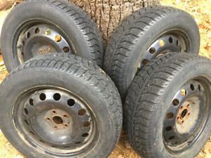Four Uniroyal Tiger Paw snow tires on steel rims
