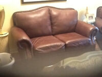 Brown leather couch and matching arm chair with foot rest