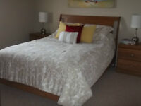 Solid oak Queen size bed with mattress and dresser with mirror.