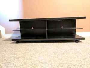 Black tv stand with glass shelving and wheels. 1 year old