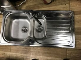 Stainless steel kitchen sink with taps