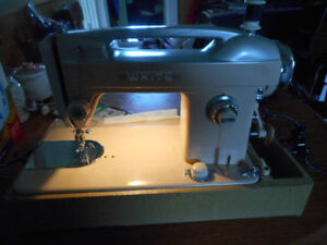 white older sewing machine works well with carrying case