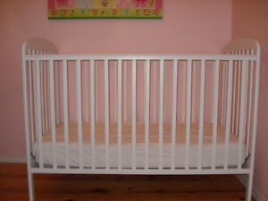 white baby crib and baby mattress
