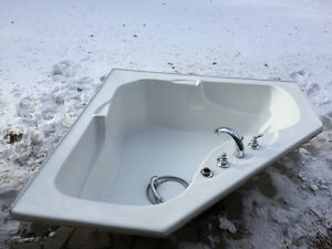 Two person corner bathtub with faucets