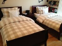 Two twin mahogany sleigh beds plus mattresses and night table