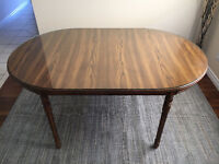 Oval shape wooden dining table with a glass top