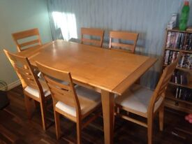 Modern dining table and six chairs, in wood. Cream coloured seats.