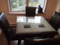 Beautiful glass top and leather chair dinning table