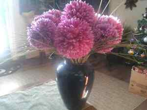 Navy blue ceramic vase filled with new purple silk flowers.