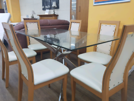 Beautiful glass dining room table with 6 leather back chairs