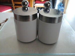 2 white canisters with attached removable spoons