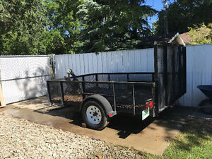 Utility trailer with folding ramp