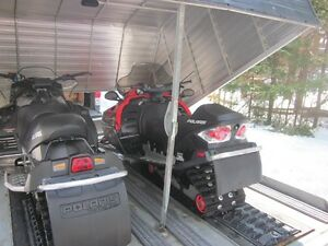 Package Deal: Two Low Mileage Polaris sleds and covered trailer