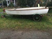 Very old wooden boat on antique custom trailer