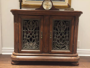 Wood hutch with interior shelf and two decorative metal doors .