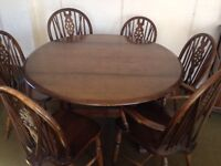 Ercol drop leaf table and four single plus two carver wheel back chairs