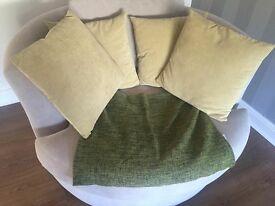 Four light green cushions and a dark green/black throw