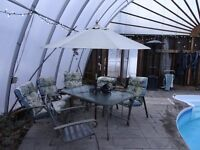 Patio table, with 8 padded chairs, and umbrella, $150.