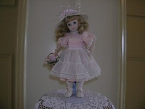 PORCELAIN CHILD DOLL IN PINK OUTFIT WITH DISPLAY STAND