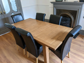 Large 6 seater wood dining room table with 6 faux leather chairs