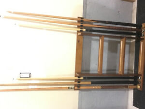 Billiards pool stick wall rack with pool cues.