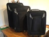 A Set of Three Wheeled Suitcases. Black. Good Condition. Will Stack inside each other.