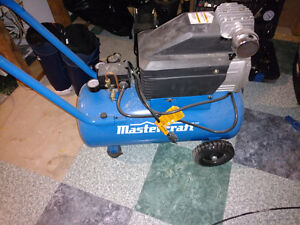 Mastercraft compressor with tools and hose reel.