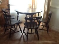 Round wooden dining table and four chairs