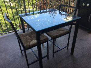 Glass top dining table with two chairs.