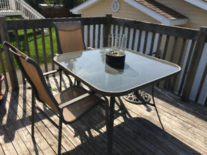 Patio table, umbrella and 4 chairs (one chair has hole in seat)