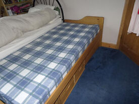 Pine single bed with roll out stirage drawers