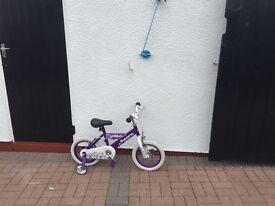Child's purple bike with stabilisers
