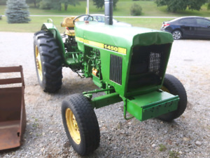 John Deere 1450 tractor with rear blade