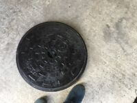 Circular cast iron manhole lid and plastic frame