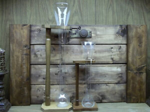 2 ALE GLASS FLASKS WITH WOODEN STANDS ONE MEASURING 25.5 INCHES