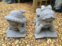 Large and medium size girl and boy figures. Concrete ornament.