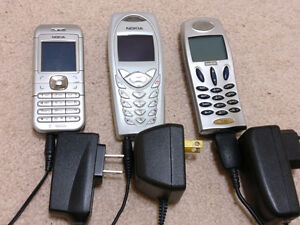 Three Old Cell Phones With Chargers