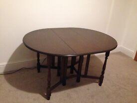 Dark wood oval drop leaf dining table
