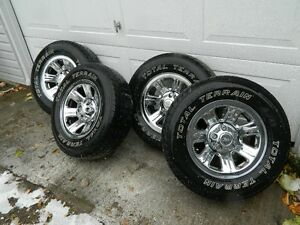 FOUR FORD CHROME RIMS AND TIRES WITH CENTRE CAPS
